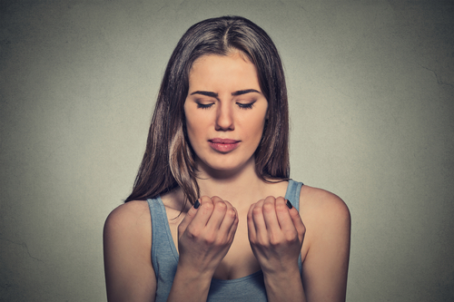 worried woman woman looking at hands fingers nails obsessing about cleanliness